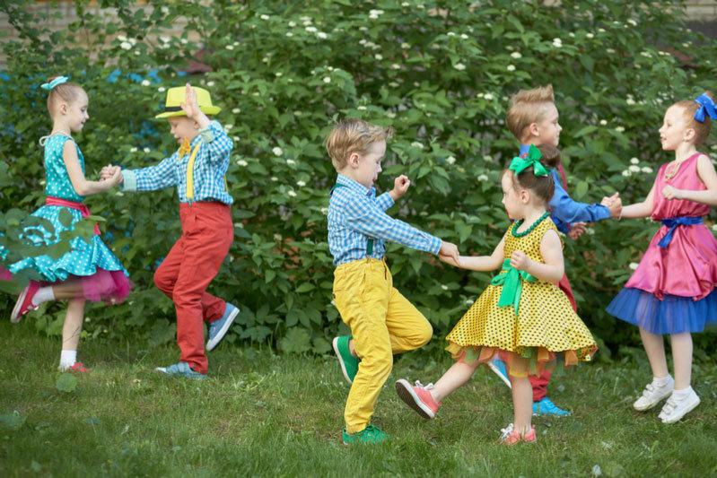 Three children couples dance on grassy lawn outdoor.